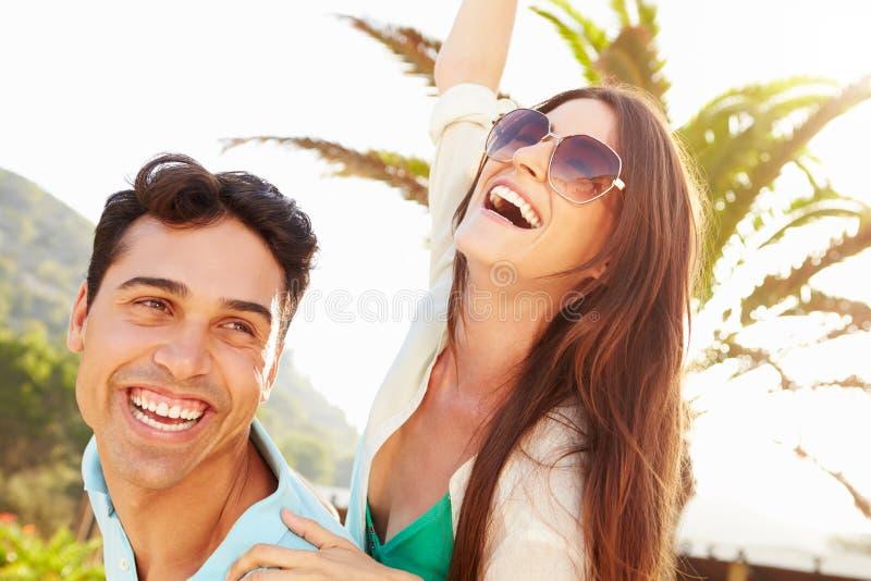 Pares jovenes que se divierten el día de fiesta de la playa junto fotos de archivo libres de regalías