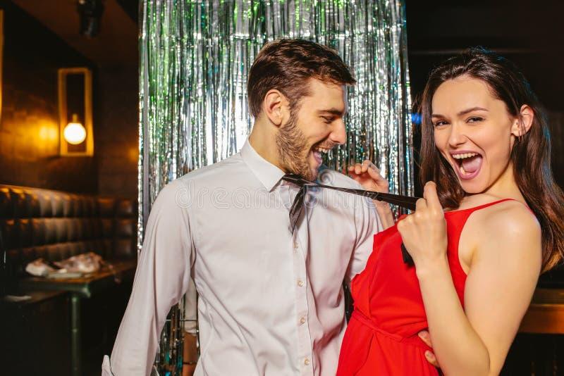 Pares jovenes que se divierten en el club nocturno Hombre y mujer en el pub foto de archivo libre de regalías