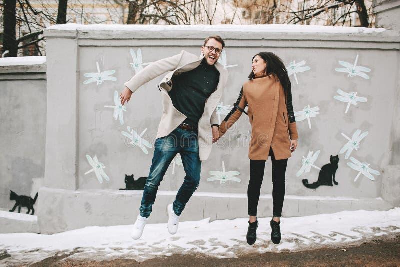 Pares jovenes que se divierten en la calle de la ciudad en invierno imagen de archivo libre de regalías