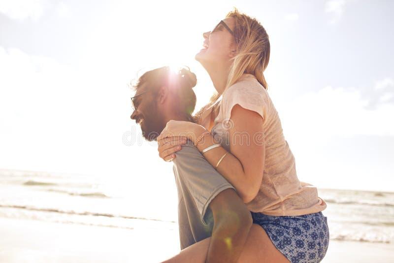 Pares jovenes que se divierten en la playa foto de archivo