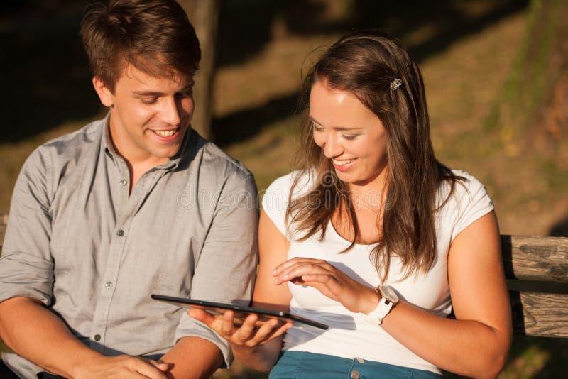 Pares jovenes que se divierten en un banco en parque mientras que socializa el ove imagen de archivo
