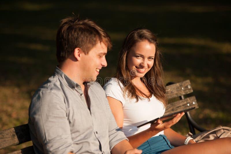 Pares jovenes que se divierten en un banco en parque mientras que socializa el ove imagen de archivo libre de regalías