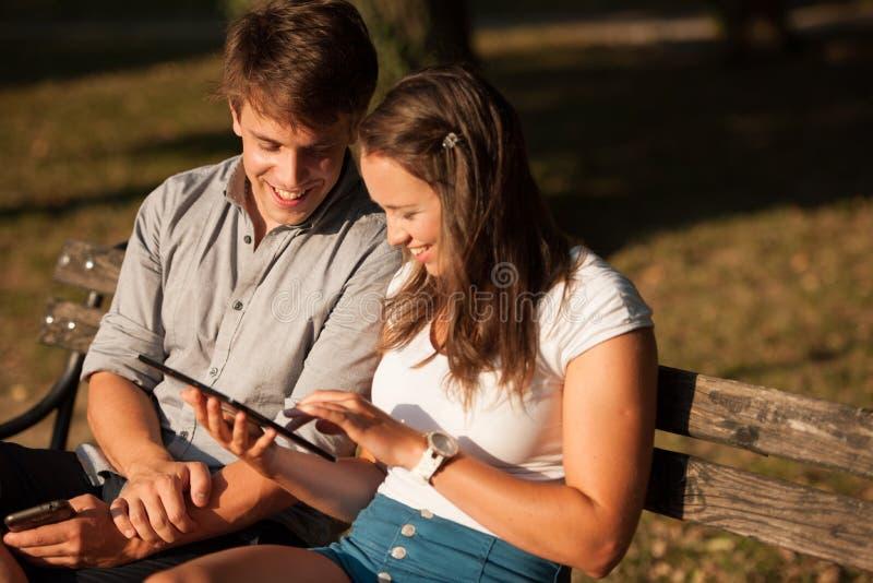 Pares jovenes que se divierten en un banco en parque mientras que socializa el ove imagenes de archivo