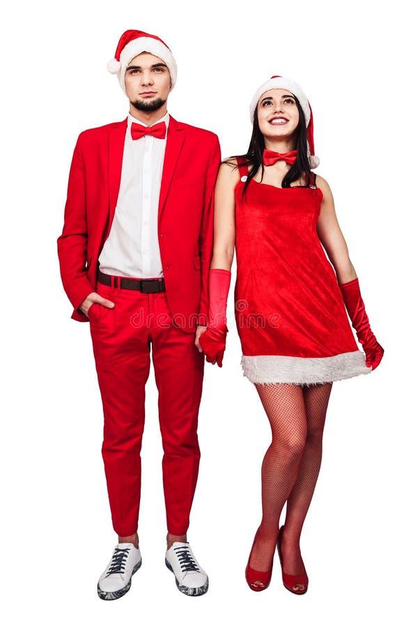 Pares jovenes que se divierten en un partido del tema de la Navidad hombre joven y mujer en trajes rojos con los sombreros de Pap imagen de archivo