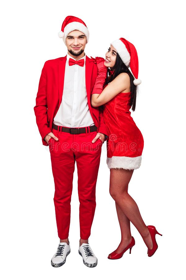Pares jovenes que se divierten en un partido del tema de la Navidad hombre joven y mujer en trajes rojos con los sombreros de Pap foto de archivo