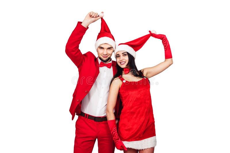 Pares jovenes que se divierten en un partido del tema de la Navidad hombre joven y mujer en trajes rojos con los sombreros de Pap fotografía de archivo libre de regalías
