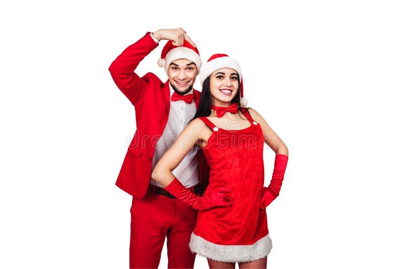 Pares jovenes que se divierten en un partido del tema de la Navidad hombre joven y mujer en trajes rojos con los sombreros de Pap imagenes de archivo