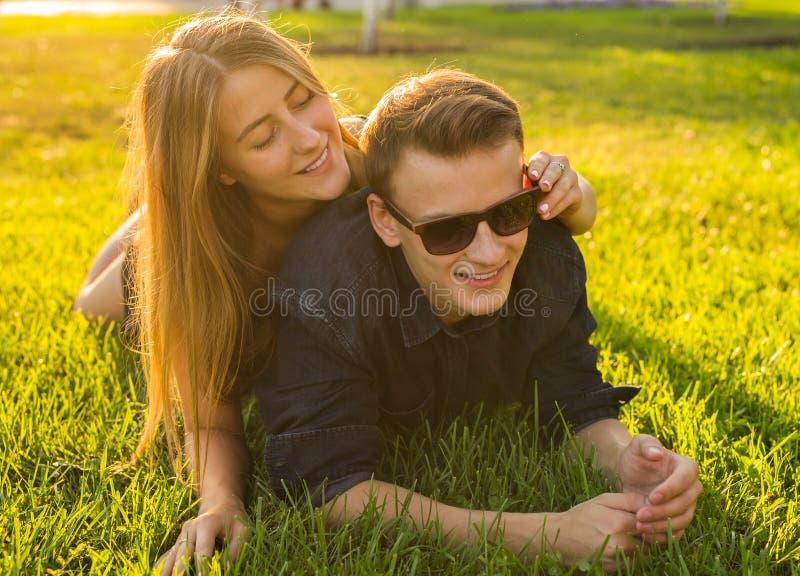 Pares jovenes que se divierten y que juegan en hierba mujer que miente sobre su amante, sonriendo fotografía de archivo