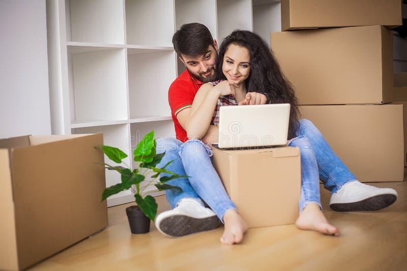 Pares jovenes que se mueven en nuevo hogar El sentarse y relajación después de unpac foto de archivo libre de regalías