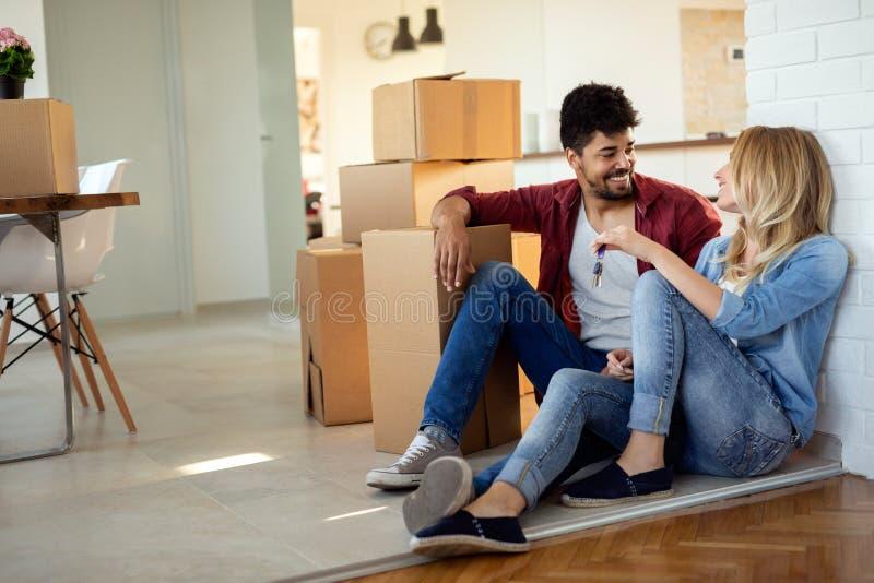 Pares jovenes que se mueven en nuevo hogar y que desempaquetan las cajas del carboard imágenes de archivo libres de regalías