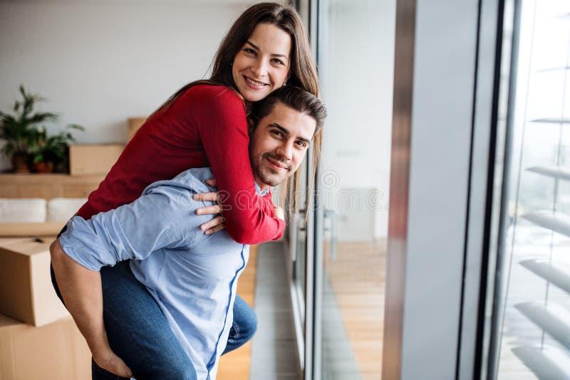 Pares jovenes que se mueven en un nuevo hogar, divirtiéndose imagen de archivo