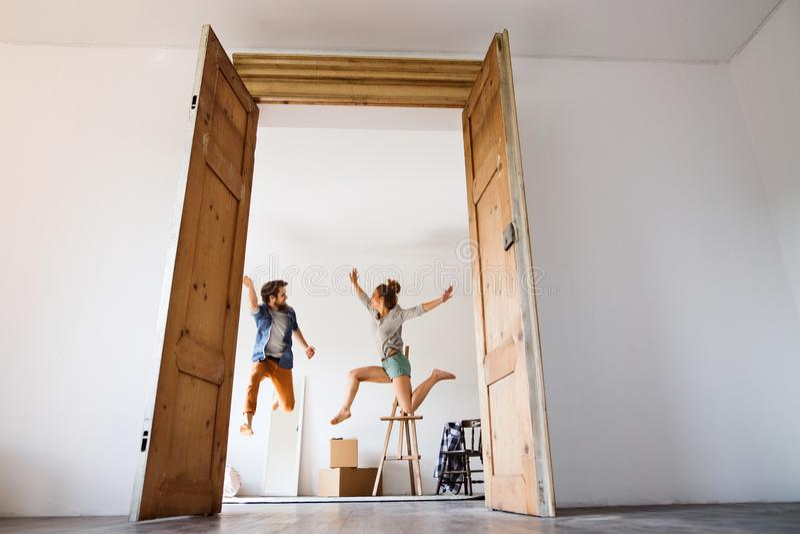 Pares jovenes que se mueven en una nueva casa, saltando encima de alto imagenes de archivo