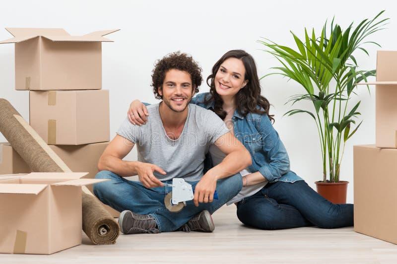 Pares jovenes que se mueven a la nueva casa imagen de archivo libre de regalías