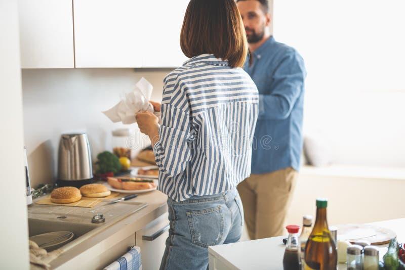 Pares jovenes que se preparan para la cena romántica en cocina imagenes de archivo