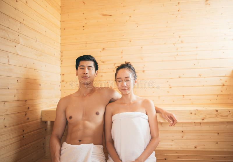 Pares jovenes que se relajan dentro de una sauna imagenes de archivo