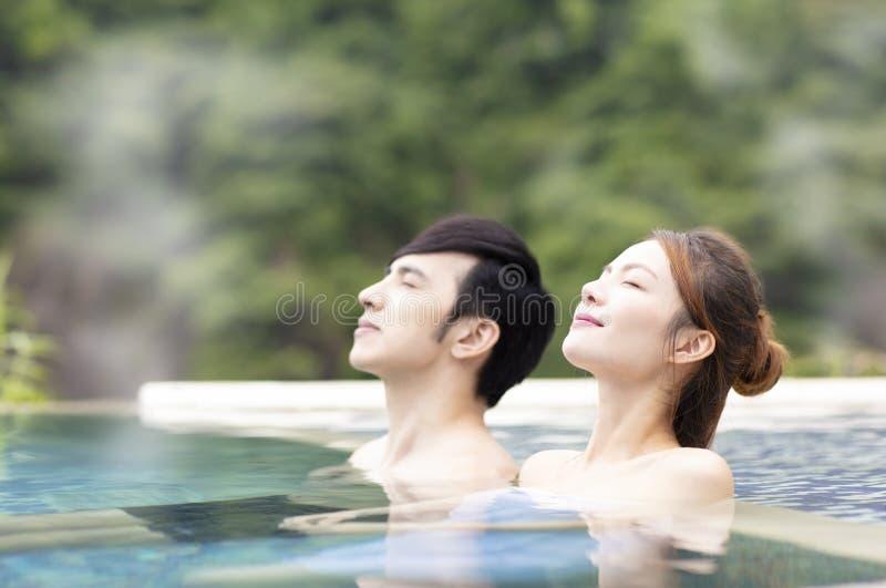 Pares jovenes que se relajan en aguas termales imagen de archivo