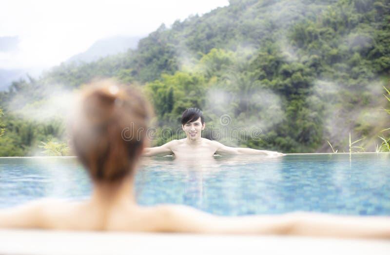 Pares jovenes que se relajan en aguas termales fotografía de archivo