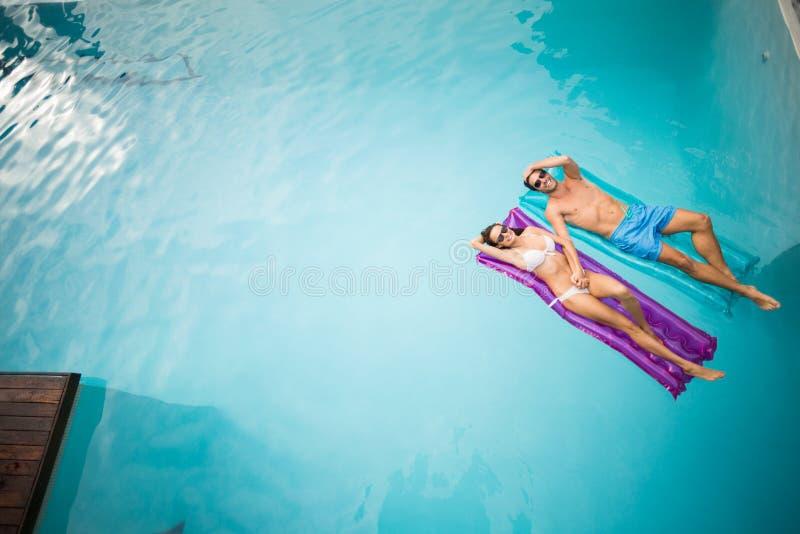 Pares jovenes que se relajan en balsa inflable foto de archivo