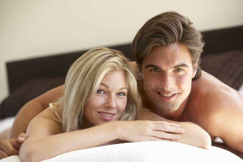 Pares jovenes que se relajan en cama fotografía de archivo