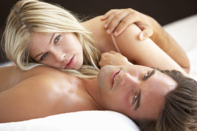 Pares jovenes que se relajan en cama fotos de archivo libres de regalías