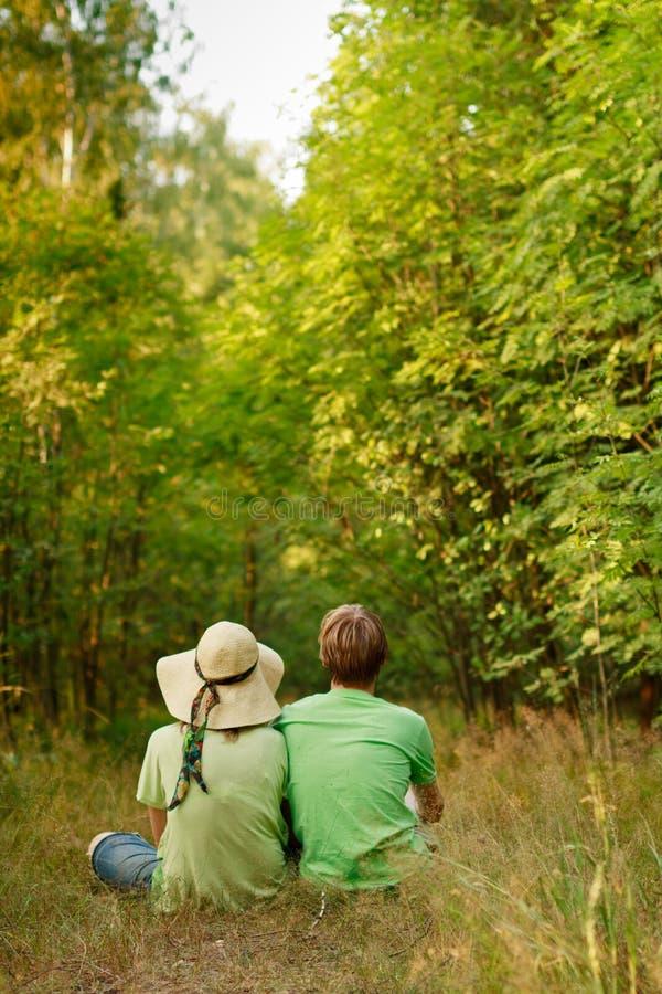 Pares jovenes que se relajan en el bosque imagen de archivo libre de regalías