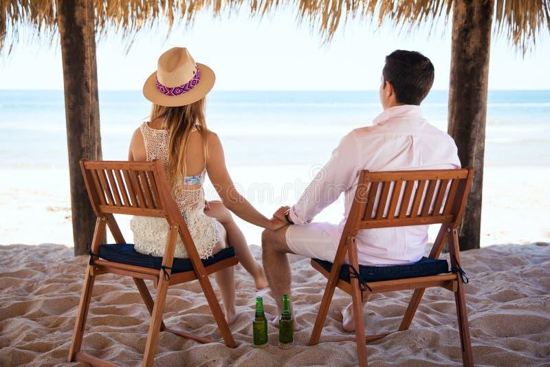Pares jovenes que se relajan en la playa fotografía de archivo