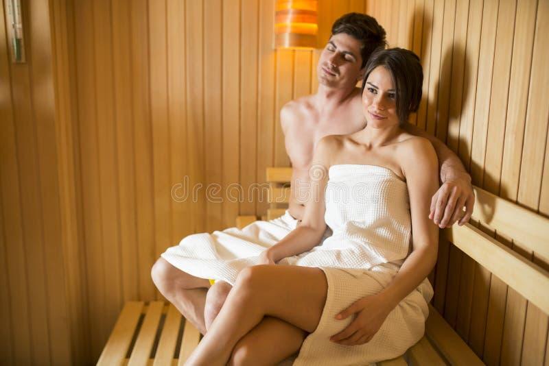Pares jovenes que se relajan en la sauna fotografía de archivo
