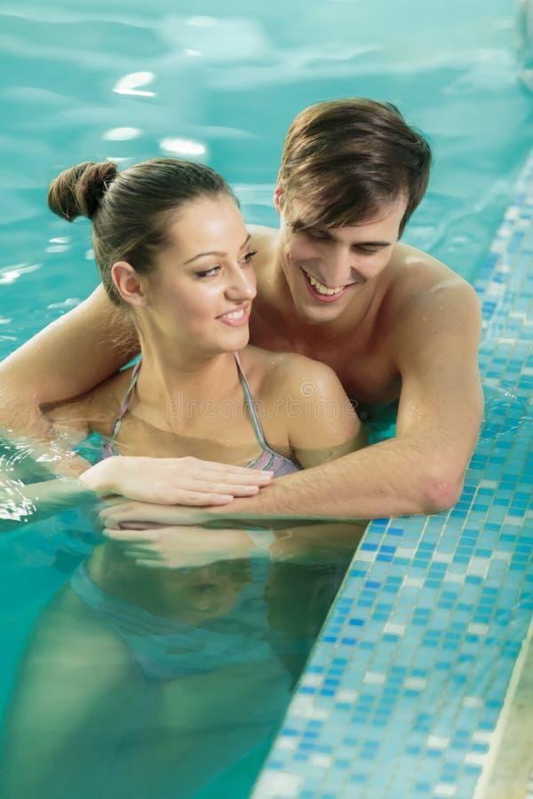 Pares jovenes que se relajan en piscina imagenes de archivo