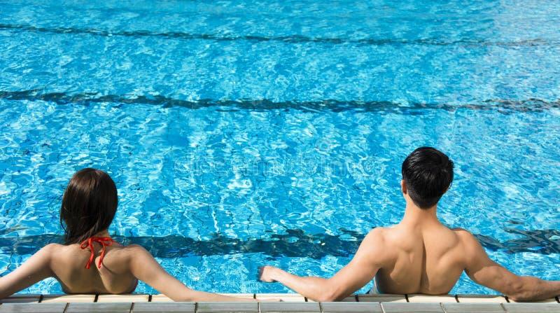 Pares jovenes que se relajan en piscina foto de archivo