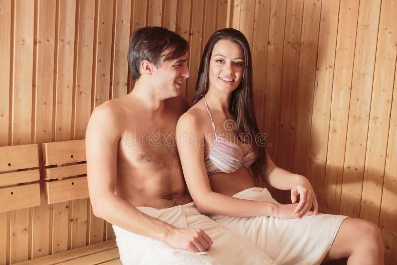 Pares jovenes que se relajan en sauna fotografía de archivo