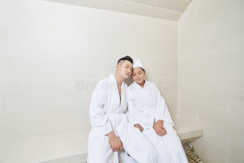 Pares jovenes que se relajan en sauna fotos de archivo libres de regalías