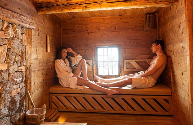 Pares jovenes que se relajan en una sauna caliente foto de archivo