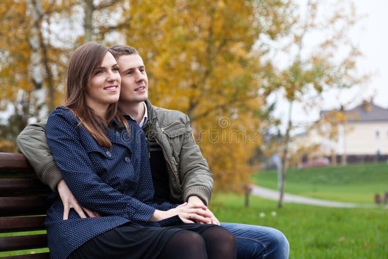 Pares jovenes que se sientan en banco en parque del otoño fotografía de archivo