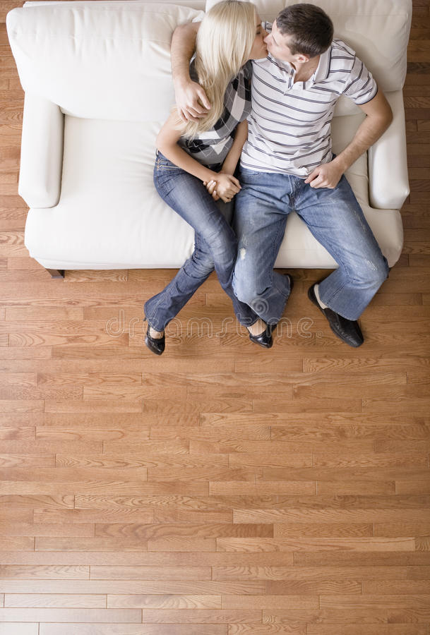 Pares jovenes que se sientan en besarse del asiento de amor fotografía de archivo