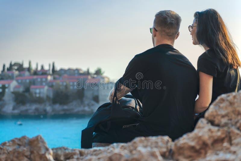 Pares jovenes que se sientan en el acantilado sobre el mar y que miran la ciudad europea en la isla foto de archivo libre de regalías