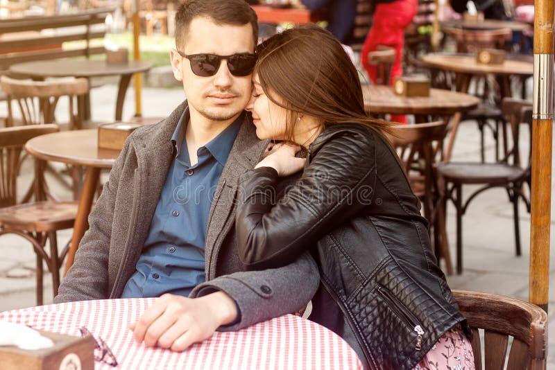 Pares jovenes que se sientan en el caf? de la calle que tiene fecha rom?ntica foto de archivo