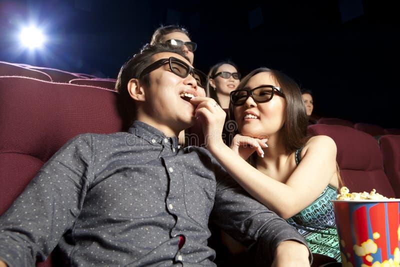 Pares jovenes que se sientan en el cine que lleva los vidrios 3d, mirando fotos de archivo