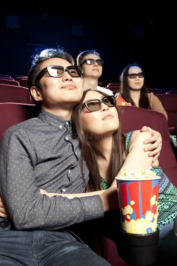 Pares jovenes que se sientan en el cine que lleva los vidrios 3d, mirando imagenes de archivo