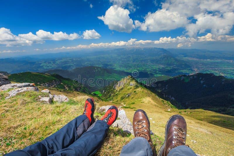 Pares jovenes que se sientan en el pico que goza de los valles y de las montañas fotografía de archivo
