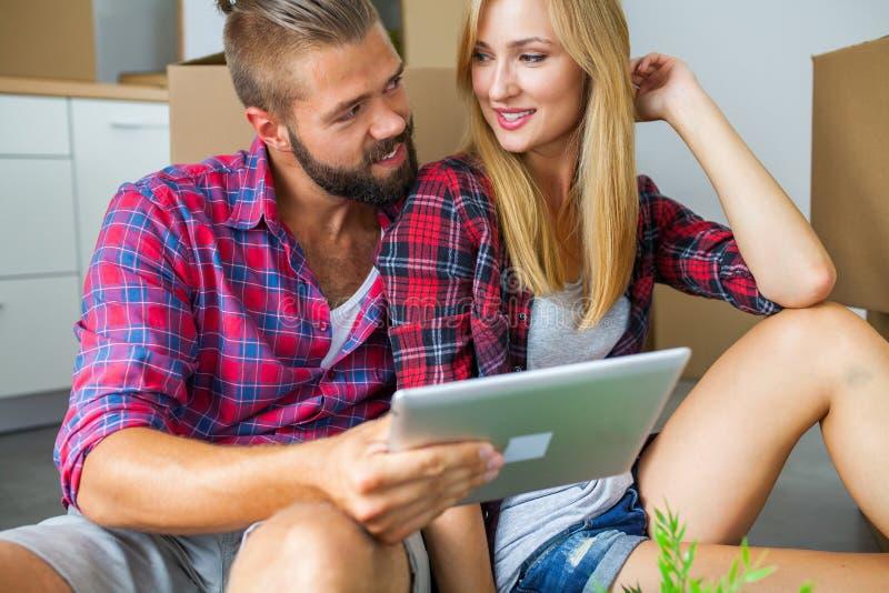 Pares jovenes que se sientan en el piso con PC de la tableta y que eligen fu imagen de archivo libre de regalías