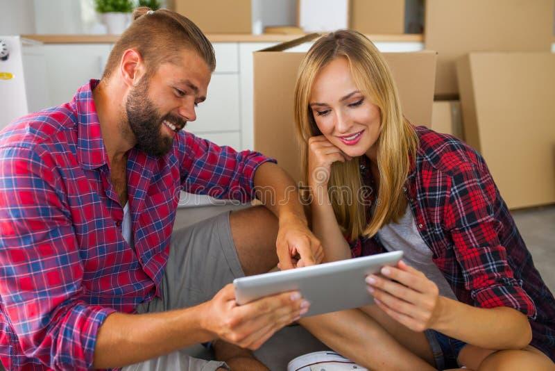 Pares jovenes que se sientan en el piso con PC de la tableta y que eligen fu fotografía de archivo libre de regalías