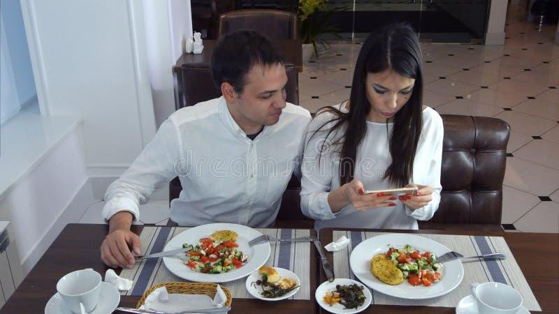 Pares jovenes que se sientan en el restaurante y que toman las imágenes de la comida con el teléfono móvil foto de archivo libre de regalías