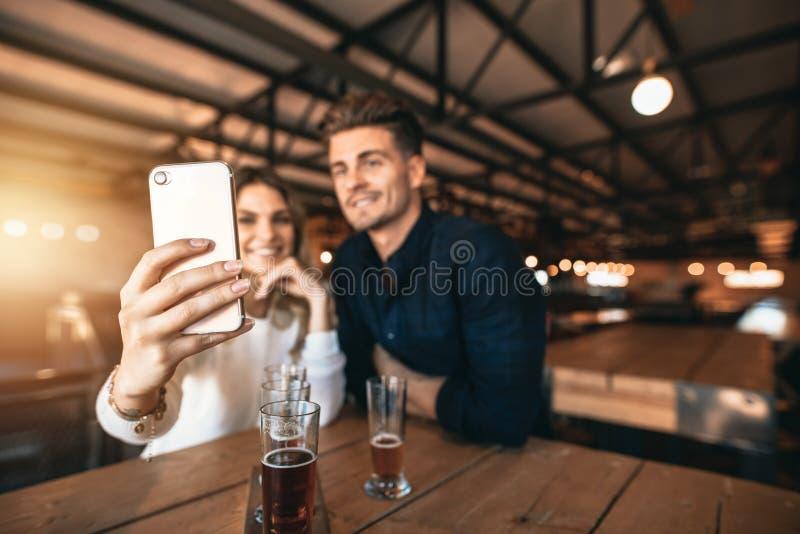 Pares jovenes que se sientan en la barra y que toman un selfie fotografía de archivo libre de regalías