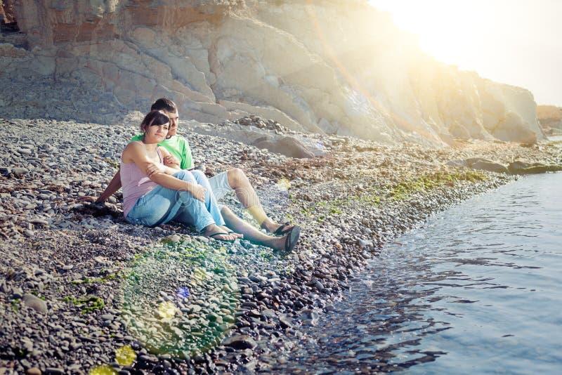 Pares jovenes que se sientan en la playa imagen de archivo
