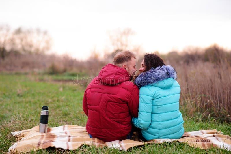 Pares jovenes que se sientan en la tela escocesa y el café de la bebida de un termo fotografía de archivo libre de regalías
