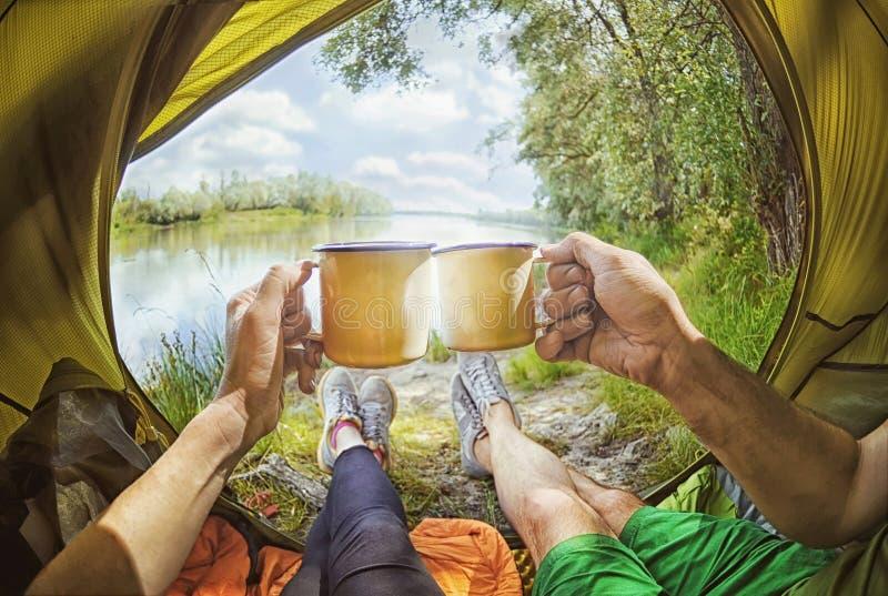 Pares jovenes que se sientan en la tienda y el té de consumición mientras que mira en el río de Desna imagen de archivo