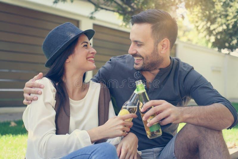 Pares jovenes que se sientan en parque y que sostienen la botella de bebida imagen de archivo