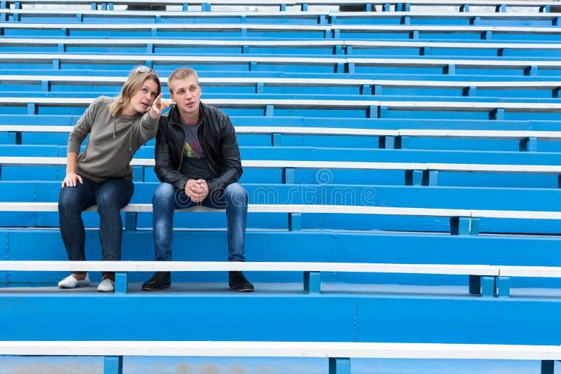 Pares jovenes que se sientan en sector vacío del estadio en la competencia Mujer que señala y que explica al hombre con los brazo imagen de archivo libre de regalías