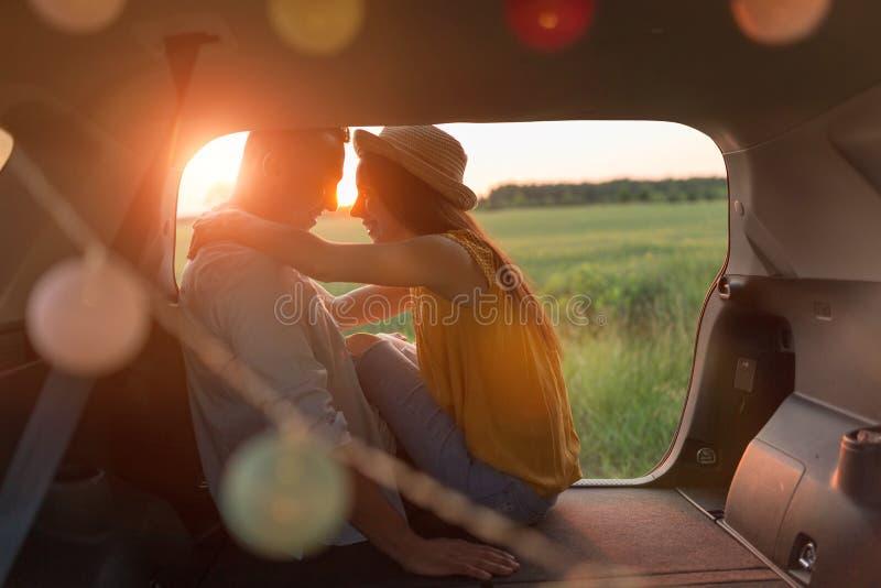 Pares jovenes que se sientan en su tronco de coche y que miran la puesta del sol fotos de archivo