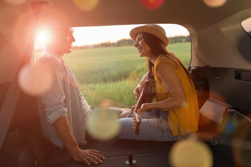 Pares jovenes que se sientan en su tronco de coche y que miran la puesta del sol foto de archivo libre de regalías